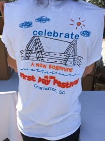 "The back of a T-shirt is shown. It says ""Celebrate a new beginning at the First Day Festival. Charleston, SC."""